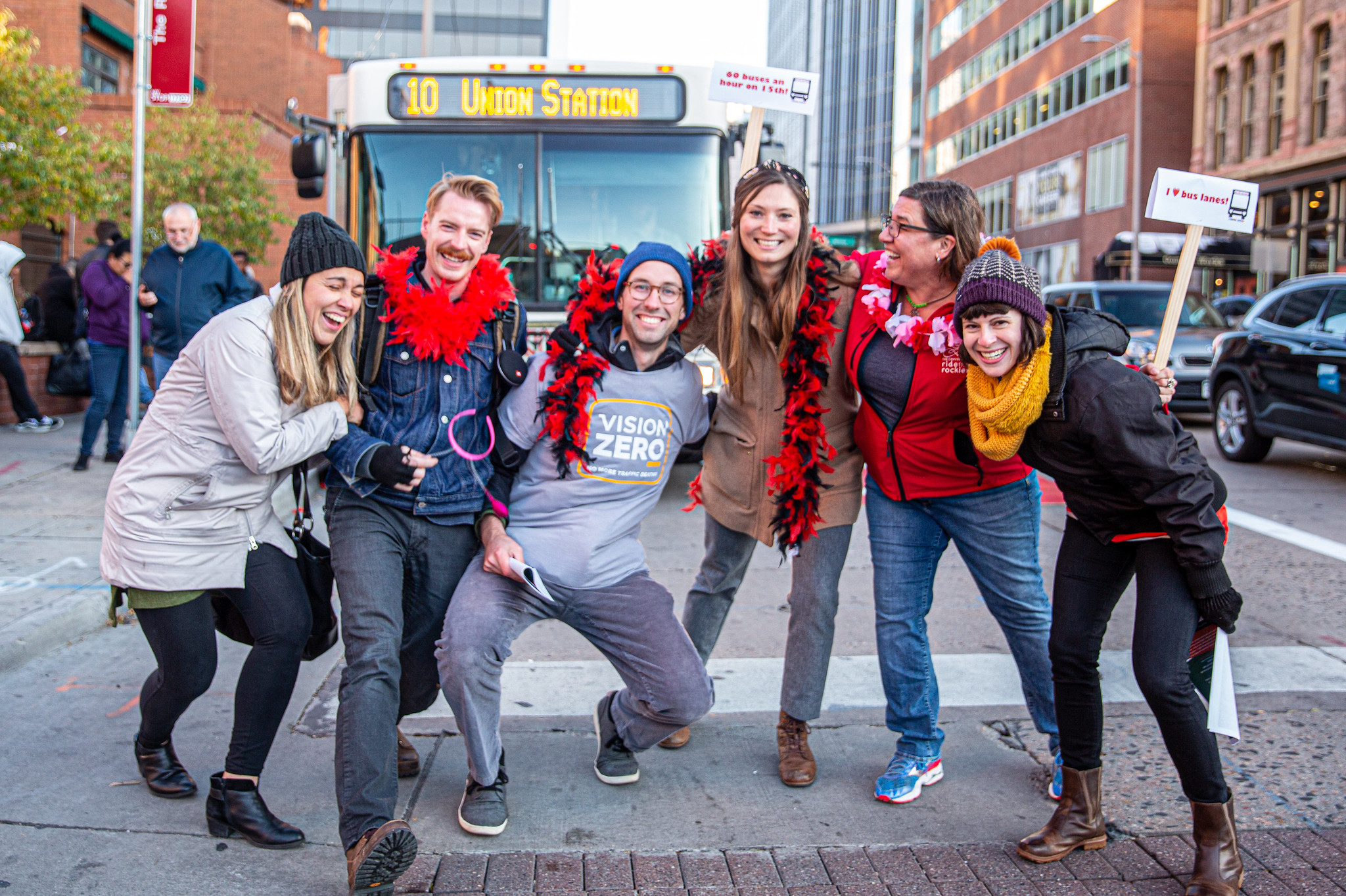 Six smiling people and an RTD bus